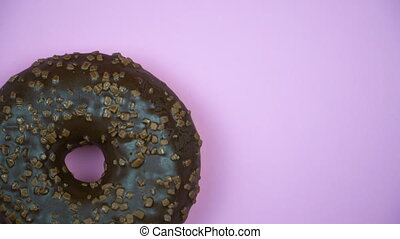 Delicious sweet donut rotating on a plate. Top view. Bright and colorful sprinkled donut close-up macro shot spinning on a pink background.