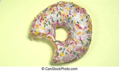 Delicious sweet donut spinning on colored background