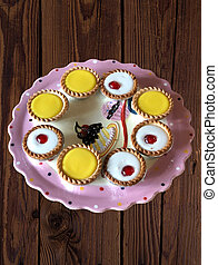 a selection of bakewell and lemon tarts on a wooden background