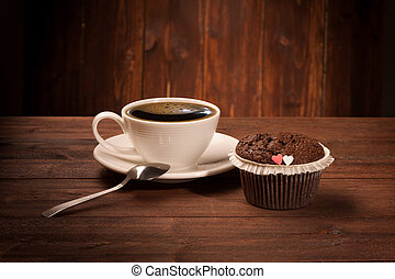 Delicious tasty cupcake and coffe cup on wooden table