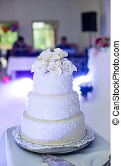 Delicious tiered white wedding cake decorated with roses at reception closeup
