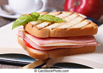 Delicious toast with ham and cheese and notebook close up