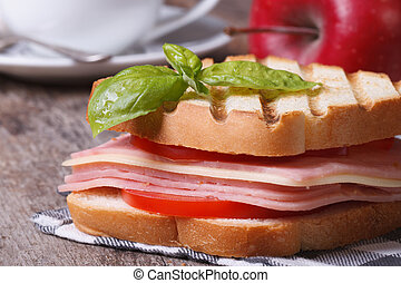 Delicious toast with ham, cheese and basil on the table