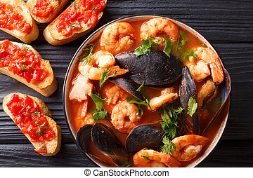 Delicious tomato soup bouillabaisse with shrimps, fish fillets and mussels closeup in a bowl. Horizontal top view