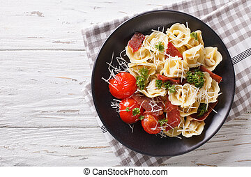 Delicious tortellini with ham, tomatoes and cheese close-up. horizontal top view