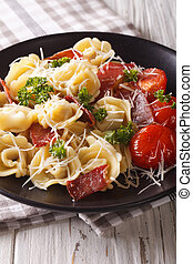 Delicious tortellini with ham, tomatoes and cheese close-up. Vertical