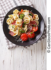 Delicious tortellini with ham, tomatoes and cheese close-up. Vertical top view