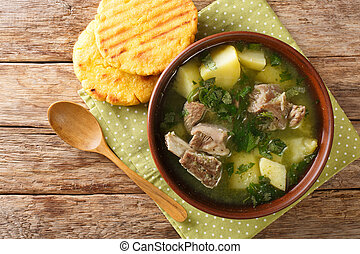 Delicious traditional soup of beef ribs with potatoes and herbs Caldo de costilla close-up in a bowl. horizontal top view