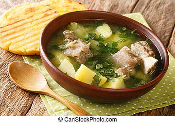 Delicious traditional soup of beef ribs with potatoes and herbs Caldo de costilla close-up in a bowl. horizontal