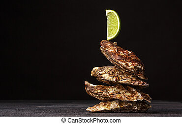 Delicious tropical sea mollusk with lime. Close-up of four beautiful closed oysters on a black background. Copy space.