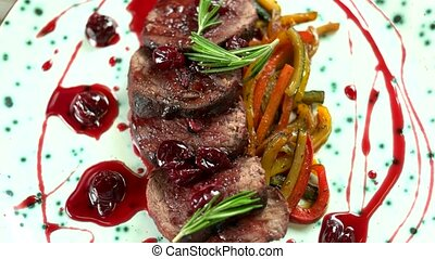Delicious veal tenderloin. Roasted meat with cherry sauce.