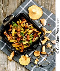 Delicious Vegetarian Roasted Chanterelles Ragout with Potatoes, Carrots, Eggplants in Black Square Pan and Raw Mushrooms closeup on Grey Napkin. Top View