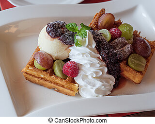 Delicious waffles with fresh fruits, ice cream and whipped cream