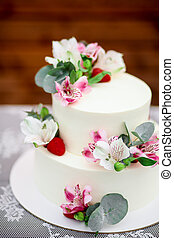 Delicious wedding cake decorated white icing with exotic flowers
