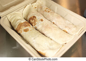 Delicious wraps in a takeout container.
