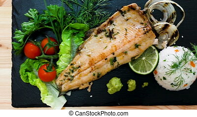 deliciously fried trout fillet with rice and greens on black plate