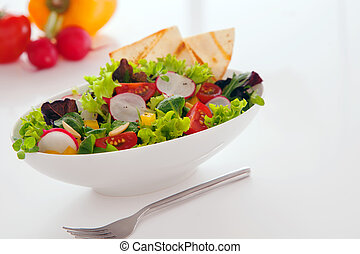 Deliciuos summer snack of fresh leafy green mixed salad with lettuce, radhish, peppers, tomato and toasted flatbread served in a white bowl