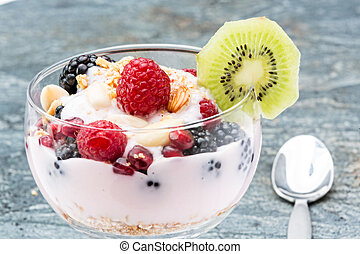 Closeup of a glass of delicous frozen berry parfait containing blackberries raspberries, pomegranate seeds and almonds, garnished with a slice of kiwifruit