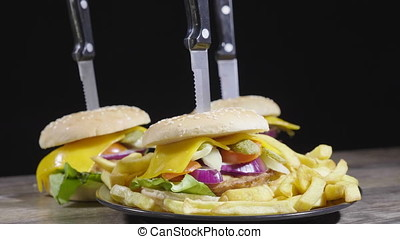 Delicous home made hamburgers with fries on wooden table over black background