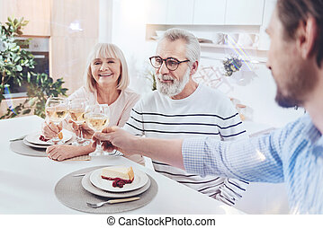 Delighetd aged couple meeting with their son at home
