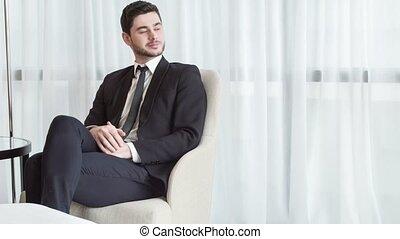 Delighetd businessman resting in his hotel room