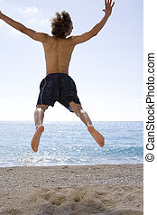 delight - boy is jumping at the beach