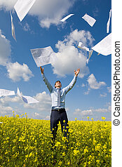 Image of happy winner throwing papers in yellow meadow
