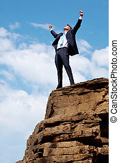 Photo of joyful businessman raising his arms upwards while standing on the rocky cliff