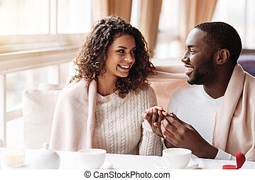 Delighted African American couple getting engaged in the cafe