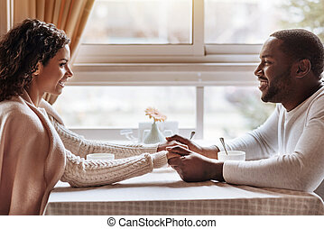 Delighted African American couple having conversation in the cafe