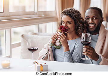 Delighted African American couple hugging in the restaurant