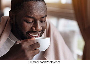 Delighted African American man enjoying the cup of tea