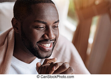 Delighted African American man having dinner in the cafe