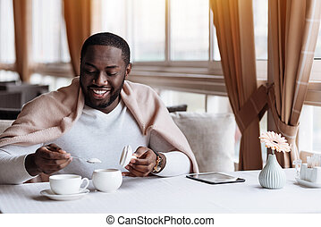 Delighted African American man having the dinner in the cafe