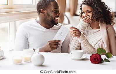 Delighted African American woman receiving a present from her boyfriend