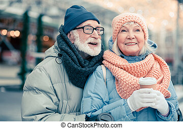 Delighted aged couple in the street smiling and looking away