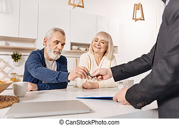 Delighted aged couple signing loan contract at home