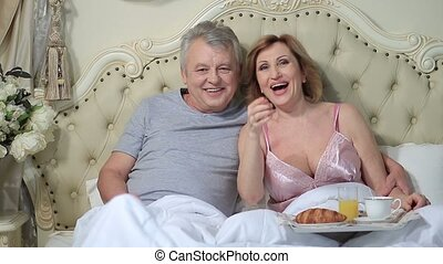 Delighted aged couple watching a movie at home
