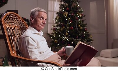 Delighted aged man reading a book