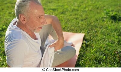 Delighted aged man resting after sport exercises in the park