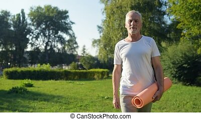 Delighted aged man walking in the park with an exercise mat...