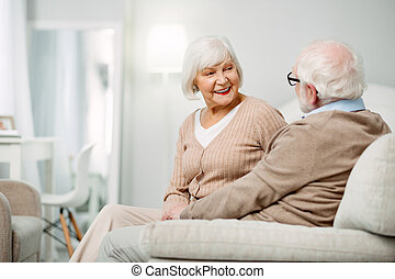 Delighted aged woman looking at her husband