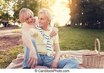 Delighted aged woman sitting behind her husband