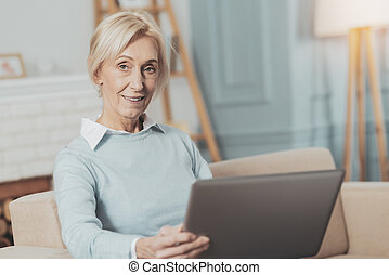 Delighted aged woman working on the laptop