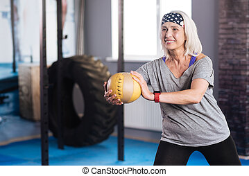 Delighted aged woman working out with a ball