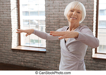 Delighted aging woman dancing in the ballroom