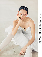 delighted and serious ballerina sitting on the floor
