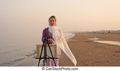 Delighted woman artist in long waving scarf stands in front of metal easel drawing seascape with brush against wet sand beach