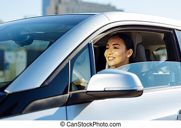 Delighted attractive woman driving to work