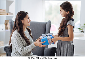 Delighted attractive woman receiving a gift